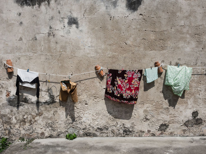 Wall - Building Feature Built Structure Architecture Day Building Exterior Domestic Clothing Wall Clothesline Laundry Standing Clothes Drying Drying Clothes Hanging In A Row Chores Still Life Weathered Urban Scene Malaysia Residential Structure Stone Wall