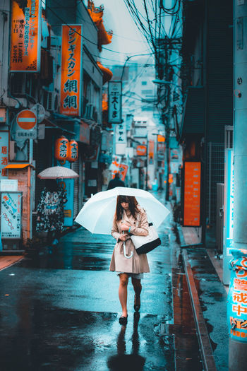 Radiant EyeEmNewHere Japan Tokyo Tokyo,Japan Adult Architecture Beautiful Woman Building Exterior Built Structure City City Life Day Full Length Happiness Lifestyles One Person Rain Real People Road Street Streetphotography Umbrella Walking Weather Women Capture Tomorrow