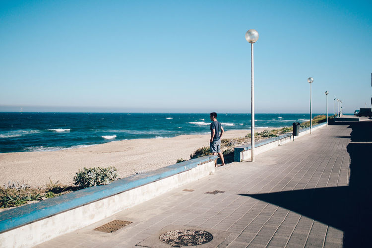 Man standing at beach by footpath during sunny day