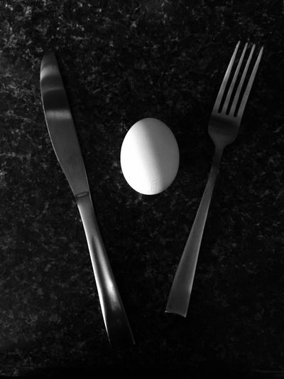High angle view of egg with fork and butter knife on table