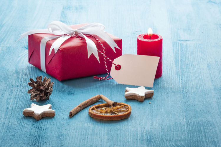 Christmas scenery with a red gift box, a lit candle, gingerbread cookies and cinnamon sticks on a blue wooden table Christmas Time Message Card Celebration Christmas Christmas Decoration Christmas Present Gift Gifting Label Tag Lit Candle Small Gift Tied Bow Winter Decoration