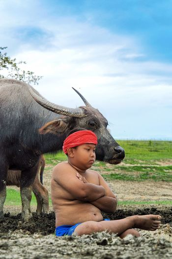 Thinking… One Animal Field One Person Sky Animal Themes Shirtless Cloud - Sky Mammal Domestic Animals Sitting Outdoors Livestock Day Real People Nature Grass Young Adult Adult People Buffalo Go Higher