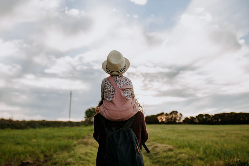 Mother carrying daughter on shoulders against cloudy sky