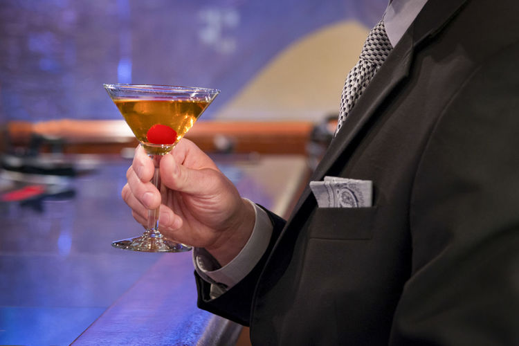 Midsection of man holding drink in martini glass