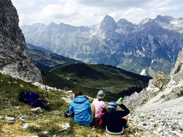 High angle view of hikers relaxing on peak while looking at mountain range