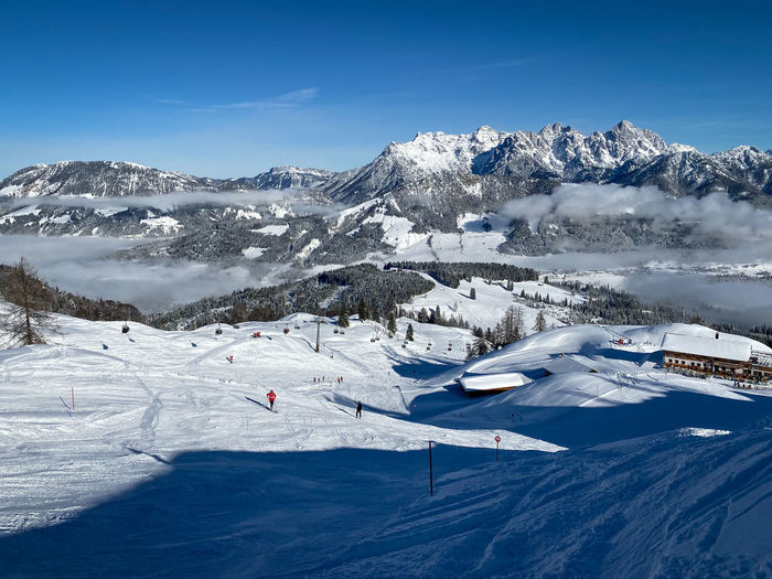 Scenic view of snow covered lofer mountains and ski slopes of fieberbrunn  against blue sky