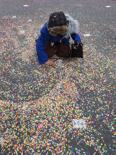 High angle view of person collecting colorful confetti on road