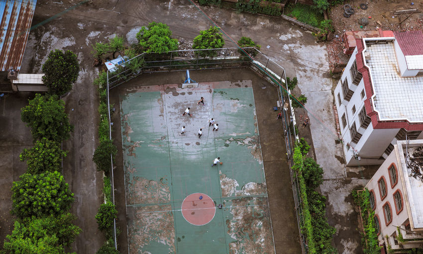 kids playing basketball at the outdoor court, Aerial view. Aerial View Architecture Basketball Building Exterior Built Structure Children City Court Kids Outdoors Players Street Student Life Teenager Tree Urban