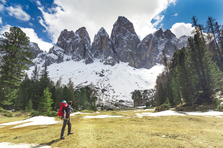 Woman walking on snowcapped mountains against sky