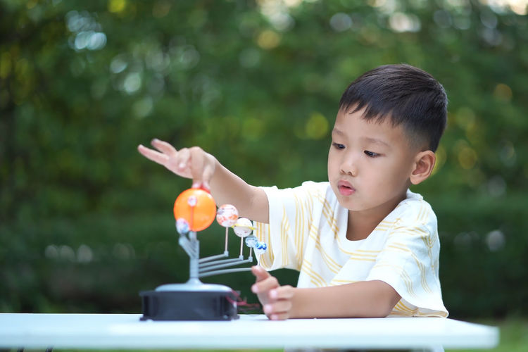 Close-up of cute boy playing with model on table in park