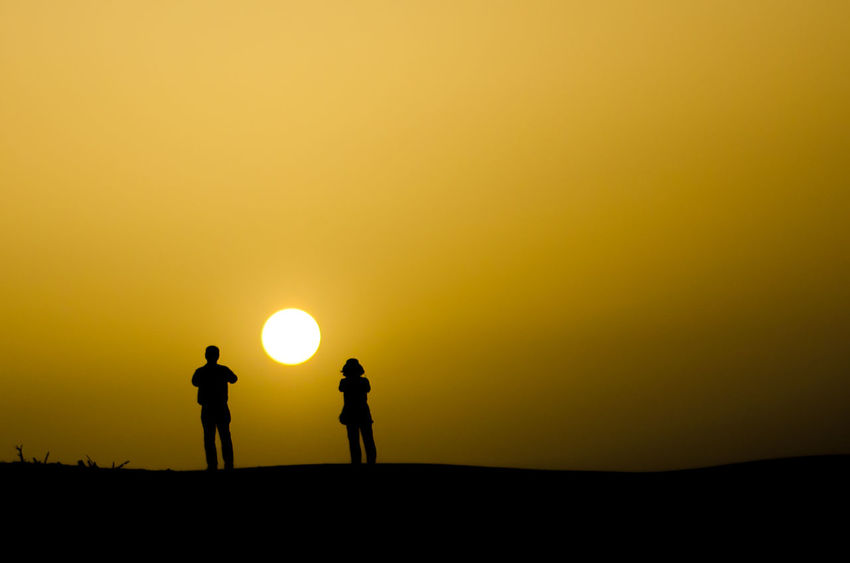 Into the light Astronomy Beauty In Nature Desert Dubai Men Nature Orange Color Outdoors People Real People Scenics Silhouette Sky Standing Sun Sunset Togetherness Tranquil Scene Tranquility Two People