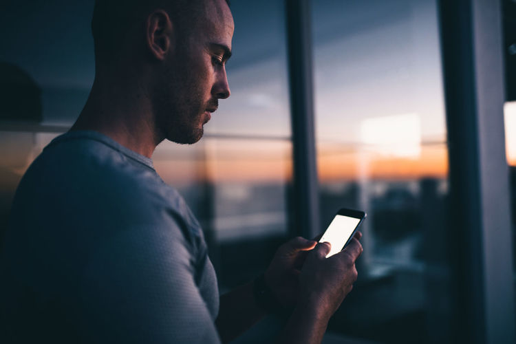 Close-up of man using mobile phone at sunset