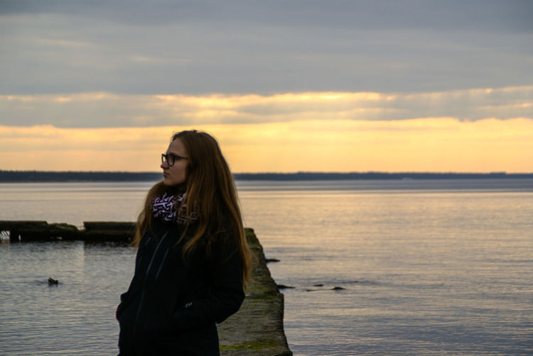 Only Women Sea Long Hair One Woman Only Adult Adults Only One Person Beach Sunset People Standing Sky Water Women Vacations Cloud - Sky Horizon Over Water Sunlight Outdoors One Young Woman Only Watching Clouds Coastline Harbor Golden Hour Perspectives On Nature