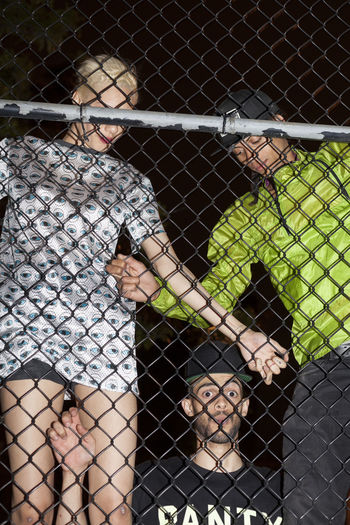 Shadow of people on chainlink fence