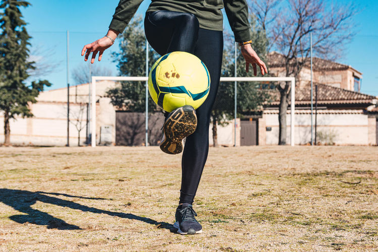 Woman controlling and kicking the ball with her feet. ground soccer field. female soccer concept.