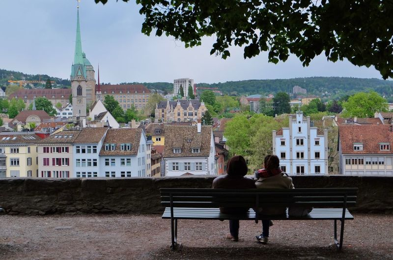Rear view of people sitting on town square