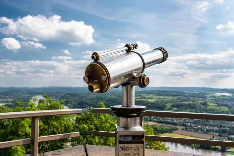 Paid single lens telescope, set on a high vantage point with a view of the city.