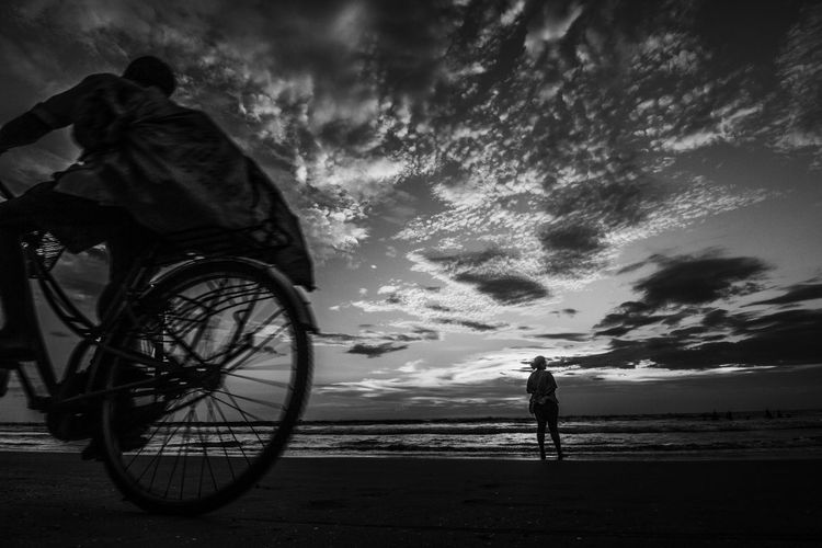 Low Angle View Of Man Riding Bicycle On Beach Against Cloudy Sky