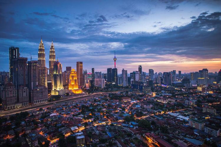 Illuminated modern buildings in city at dusk