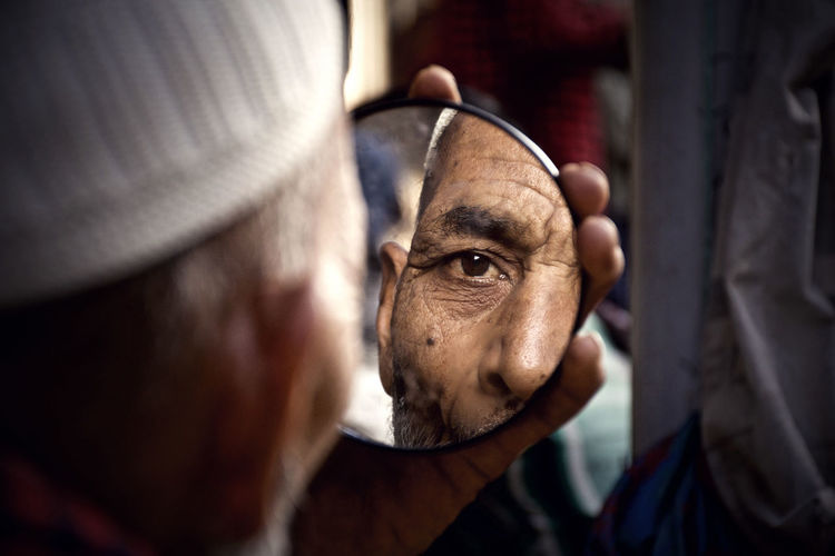 Close-up of man holding mirror with reflection