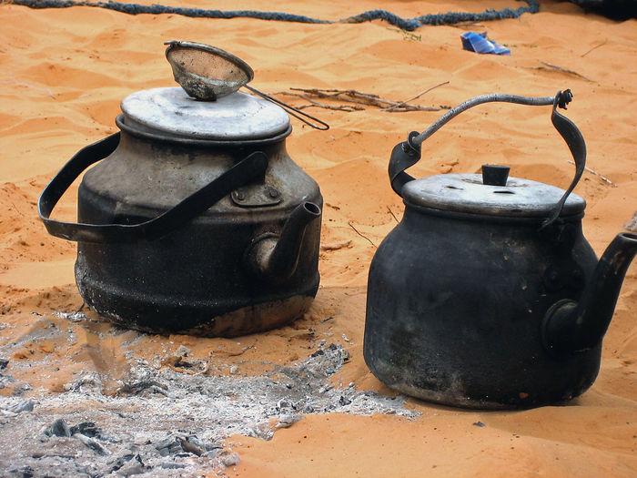 High angle view of burnt kettles on sand in desert