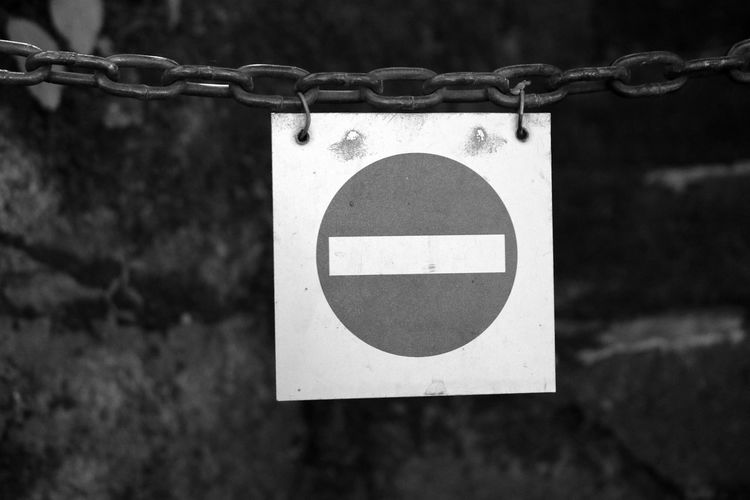 Close-up of metallic no entry sign hanging from chain
