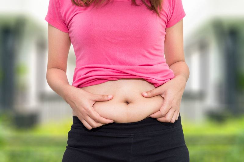 Midsection of woman pinching her belly outdoors