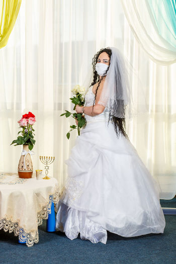 Woman wearing mask against white background