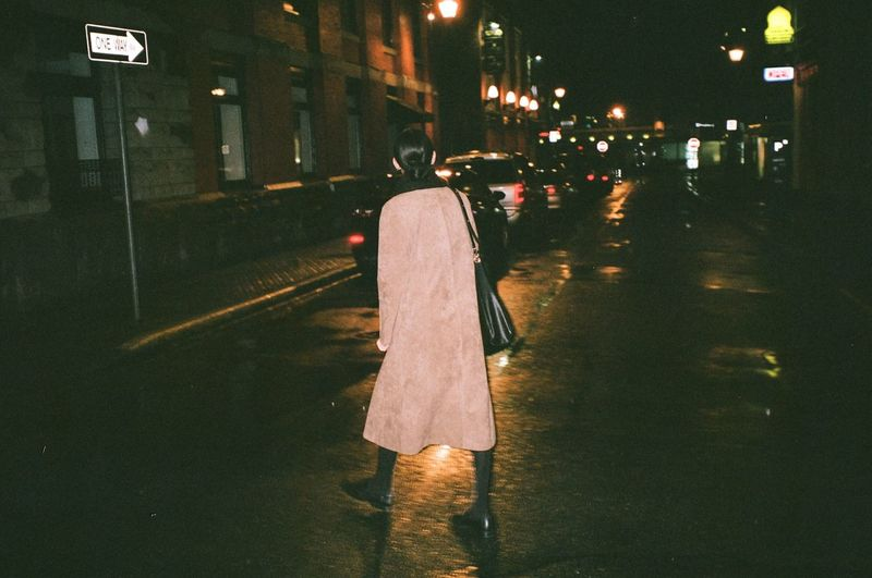 Rear view of woman walking on illuminated street at night