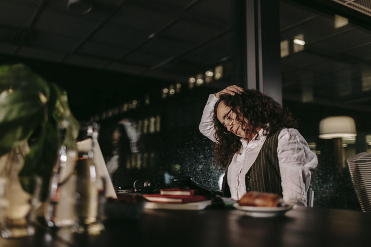 Woman sitting at restaurant table in cafe