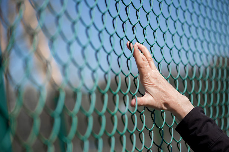 Abstract Adult Adults Only Backgrounds Baseball - Sport Baseball Helmet Baseball Player Broken Dreams Chainlink Fence Close-up Day Fingers Human Body Part Human Body Parts Human Hand Leisure Activity One Person Outdoors People Playing Field Real People Refugees Sport Team Sport Woman Out Of The Box