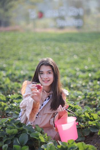 Portrait of smiling woman holding plant