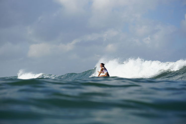 Side view of woman surfing in sea against sky