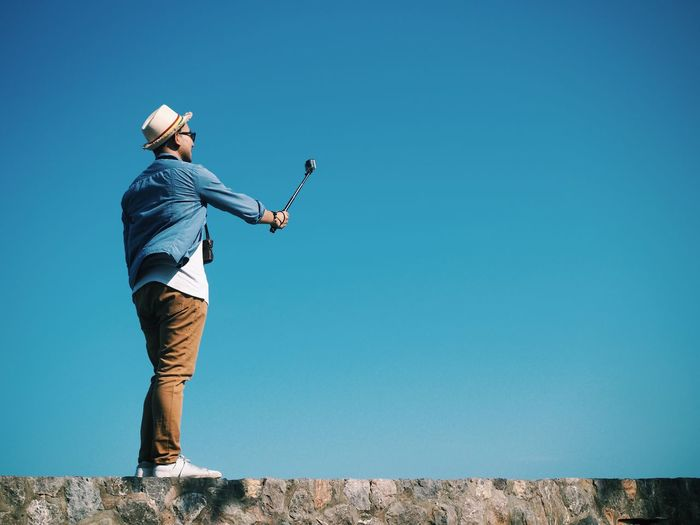Low angle view of man taking selfie with monopod on stone wall against clear blue sky
