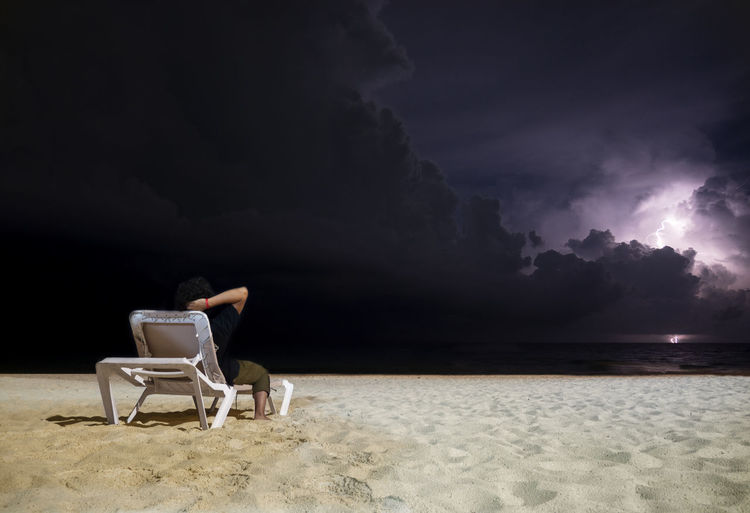 Man sitting on chair at beach against sky at night