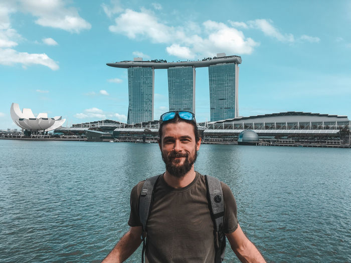 Portrait of smiling man against marina bay sands in city
