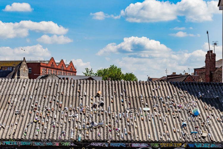 Cans on roof against cloudy sky