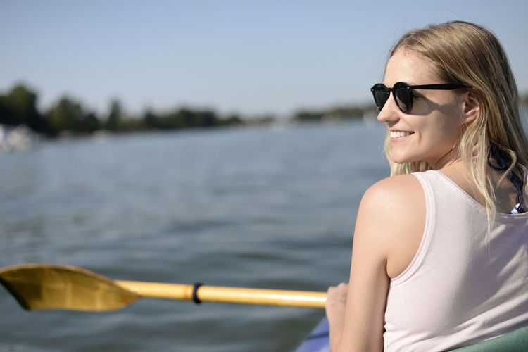 woman in kajak Woman Boat Paddle Boat Kayak Paddle Paddling Young Women Beautiful Woman Happy Contentment Relaxing Holiday Summer Lake River Water Fitness Millennials Blond Hair Leisure Activity One Person Women Nature Outdoors Sunglasses Glasses Vacations Lifestyles Day