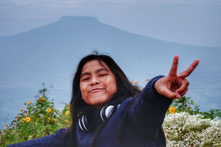 Portrait of smiling girl gesturing peace sign against mountains