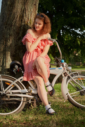 Full length of woman sitting on bicycle against trees