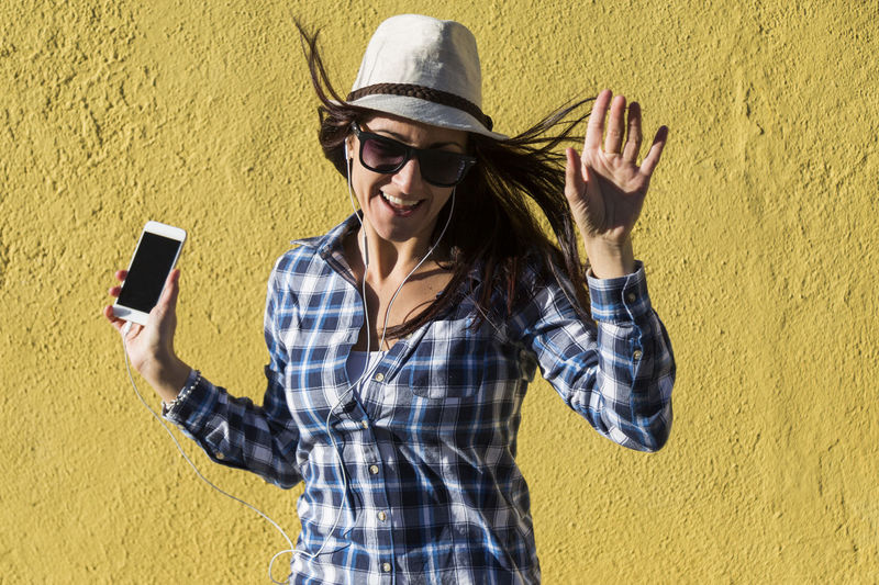 Young woman using mobile phone against yellow wall