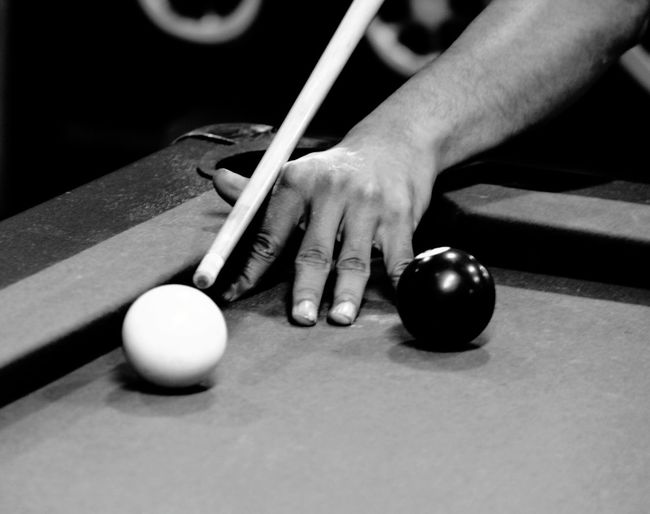 Hand aiming at cue ball on pool table