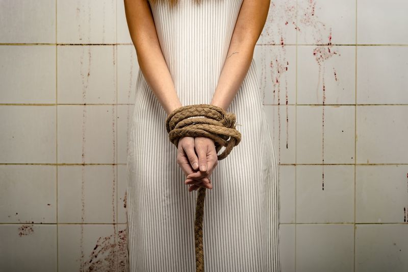Midsection of woman tied hands standing by wall