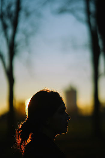 Silhouette woman against sky during sunset