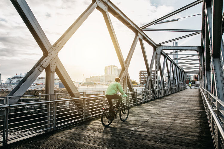 Man riding bicycle on footbridge in city