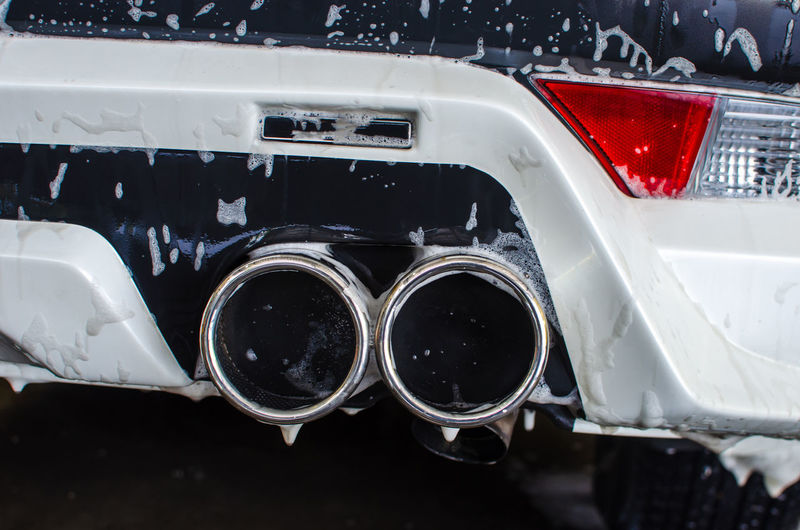 Close-up of exhaust pipes of wet car
