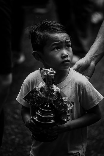 Boy Looking Away While Holding Statue Outdoors