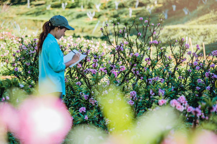 Side view of female researcher examining flowers on land