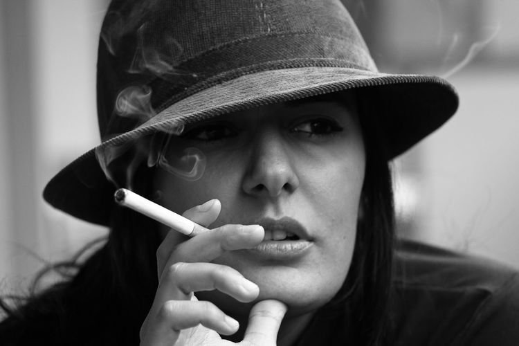 Close-Up Of Young Woman Looking Away While Smoking Cigarette