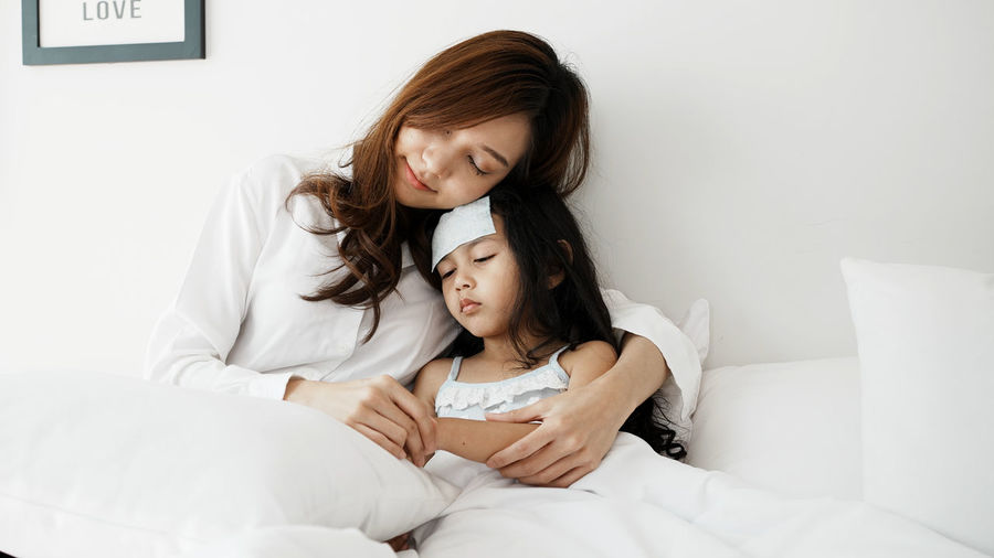 Portrait of mother and daughter sitting on bed